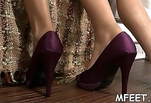 Sexy footjob on a red sofa indoors